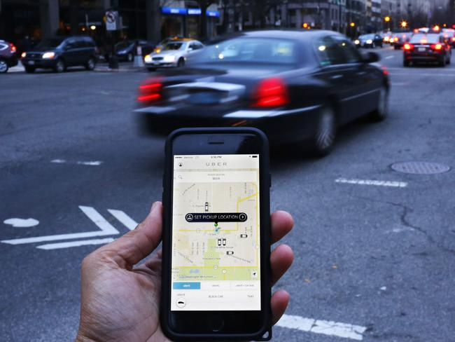 (FILES) This file photo taken on March 25, 2015 shows an UBER application shown as cars drive by in Washington, DC.  A driverless, electric car is only a swipe away in the cities of the future, where pollution clampdowns and rapid advances in technology will transform the way we travel, despite lagging infrastructure. As more and more countries announce a phasing-out of pure petrol and diesel cars, early versions of tomorrow's models are already on the streets: hybrid cars, fully electric motors and vehicles that can partially drive themselves.  / AFP PHOTO / Andrew Caballero-Reynolds