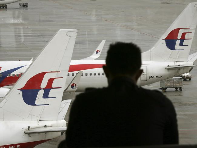 Unsolved mystery ... visitor looks out from the viewing gallery as Malaysia Airlines aircraft sit on the tarmac at the Kuala Lumpur International Airport.