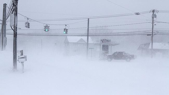 A vehicle drives through a barely visible intersection in Stafford, NY.