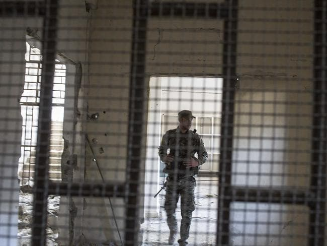 A members of the U.S.-backed Syrian Democratic Forces (SDF) walk inside a prison built by Islamic State fighters at the stadium that was the site of IS fighters' last stand. Picture: Asmaa Waguih