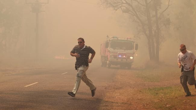 Two men make a dash for it as a large bushfire moves into Londonderry. Picture: Stephen Cooper