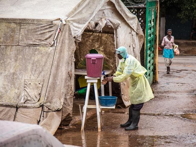 Cleaning hands ... a health worker uses chlorinated water before entering a Ebola screening tent, at the Kenema Government Hospital. Picture: AP/ Michael Duff