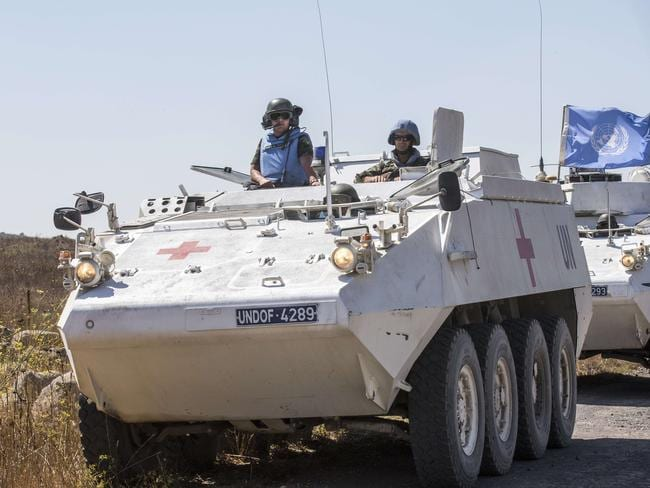 Peacekeepers ... An armoured ambulance of the United Nations Disengagement Observer Force (UNDOF) waits next to other UN vehicles in the Israeli-annexed Golan Heights as they wait to cross into the Syrian side of the Golan.