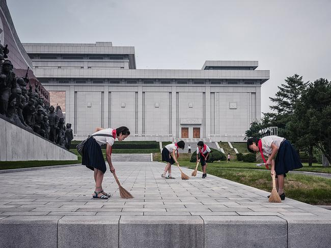 Women working to keep a memorial spotless in Pyongyang. Picture: Michal Huniewicz /Exclusivepix Media