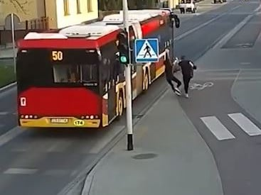 The girl's friend shoves her just as the bus passes them.