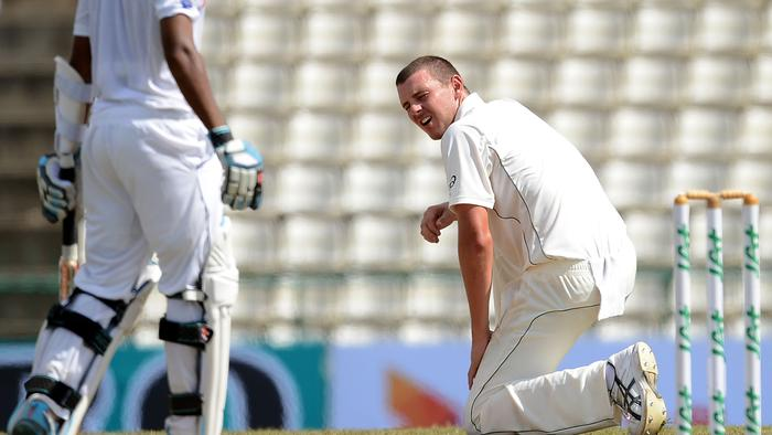 Australia's Josh Hazlewood (R) rises after delivering a ball during the third day of the opening Test match between Sri Lanka and Australia at the Pallekele International Cricket Stadium in Pallekele on July 28, 2016. / AFP PHOTO / LAKRUWAN WANNIARACHCHI