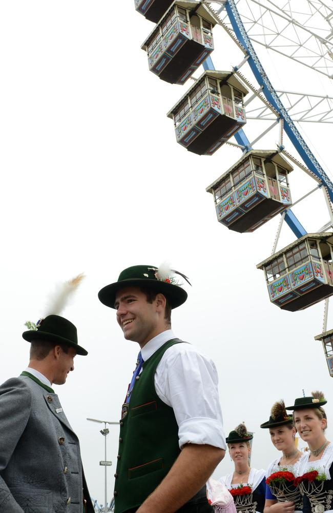 Crime rate fallen this year ... Members of a brass musician band and a local costume group dressed in typical Bavarian clothes wait beside the ferris wheel at the traditional Bavarian Oktoberfest festival at the Theresienwiese in Munich. Picture; Christof Stache