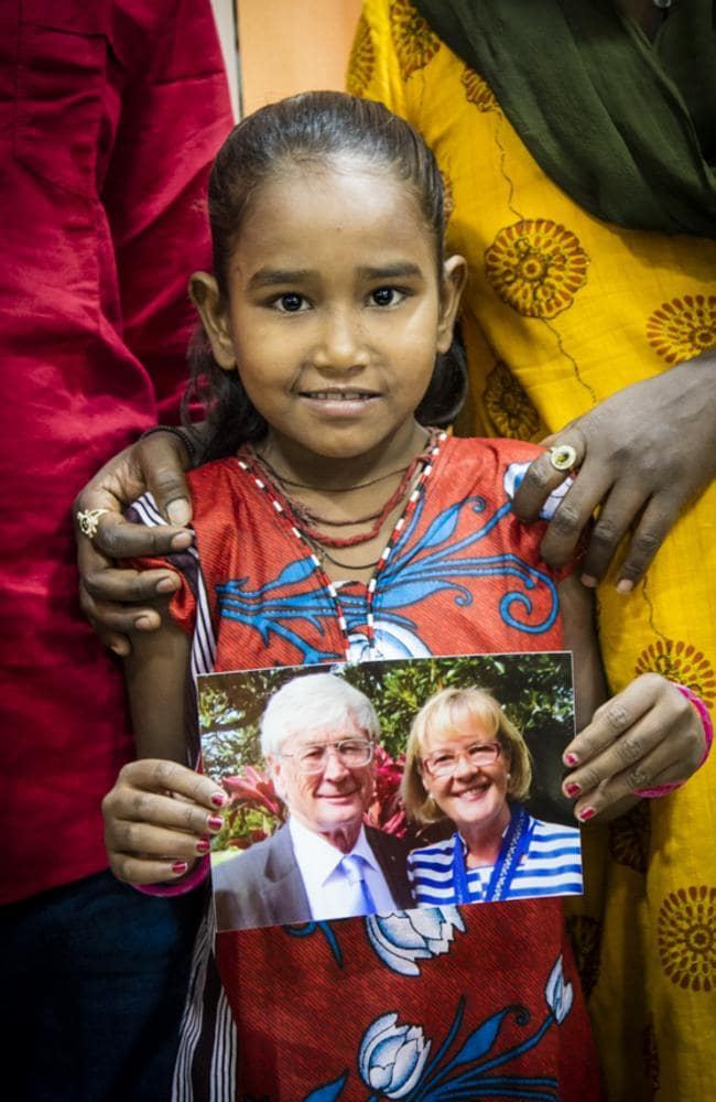 What a wonderful Christmas story! Divya, all dressed up in her new clothes, holding up a photo of Dick and Pip Smith. Picture: Chris Bray