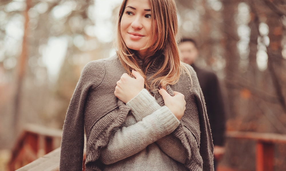 young woman in cozy warm cardigan walking outdoor with boyfriend