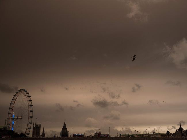 The sky darkens over the London Eye and the Houses of Parliament in London after Hurricane Ophelia battered the UK. Picture: AFP/Chris J Ratcliffe