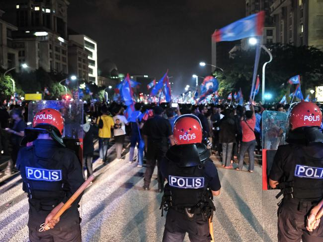 Malaysian police officers stand alert as opposition party supporters hold a rally in Putrajaya, Malaysia. Picture: AP