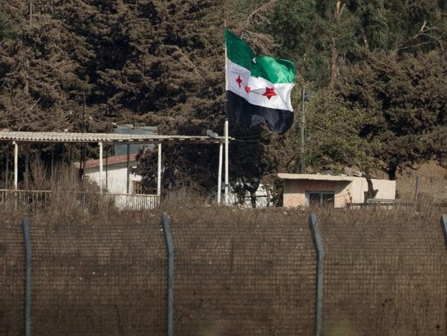A picture taken from the Golan Heights shows a pre-Baath Syrian flag, now used by the Syrian opposition, flying over the border crossing.