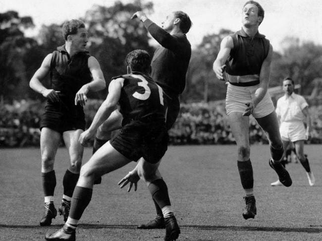 Ron Barassi, in his famous No. 31, prepares to pounce as Brian Gilmore (right), Don Cordner and Stuart Spencer contest a loose ball in the 1954 Grand Final.