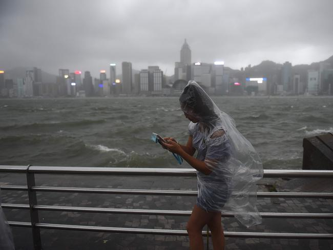 A woman wanders along Victoria Harbour during heavy winds and rain brought on by Typhoon Hato in Hong Kong. Picture: AFP
