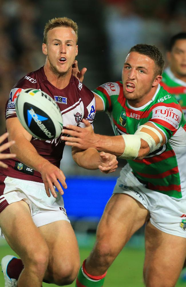 Daly Cherry-Evans offloads as Sam Burgess closes in during the round 2 clash between the Sea Eagles and Rabbitohs.