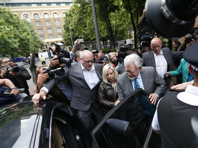 Facing jail time...Veteran entertainer Rolf Harris, centre right, accompanied by his daughter Bindi, centre, and security, leave Southwark Crown Court surrounded by members of the media in London. Picture: AP