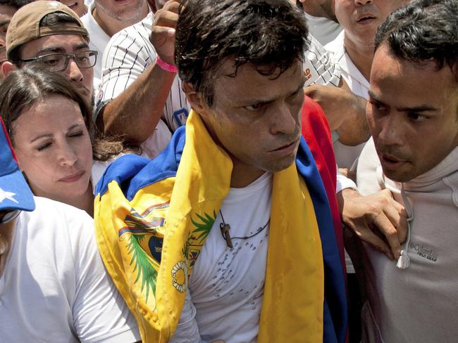 Opposition leader Leopoldo Lopez, second from right, draped in a Venezuelan national flag just before he surrendered to national guards, in Caracas, Venezuela in February 2014.