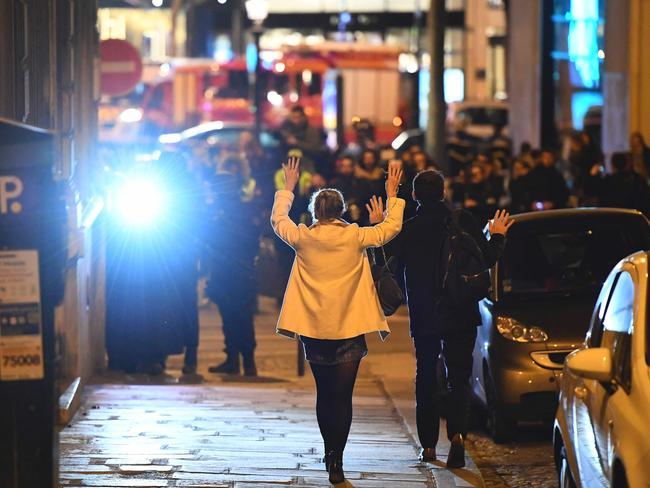 People hold their hands up as they walk towards police officers before being controlled near the site of the shooting.