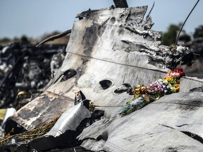 The parents of an Australian victim of the MH17 crash left flowers on the wreckage in July 2014. Picture: AFP/Bulent Kilic