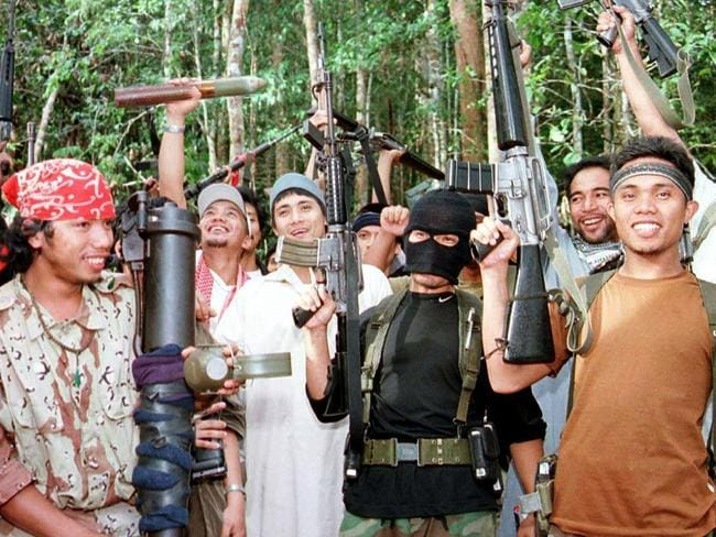Heavily-armed members of extremist group Abu Sayyaf pictured at their jungle hideout in the mountains of Sumisip, on the southern Philippine island of Basilan, in 2000. Picture: Supplied