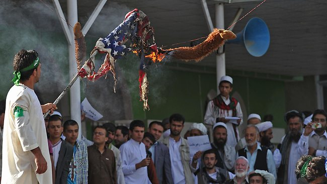 Afghan demonstrators burn an effigy of US President Obama and a US flag during a protest, against an anti-Islam movie and a French Magazine which published Muhammad Prophet's cartoons, in Kabul on September 21, 2012. AFP PHOTO/Massoud HOSSAINI