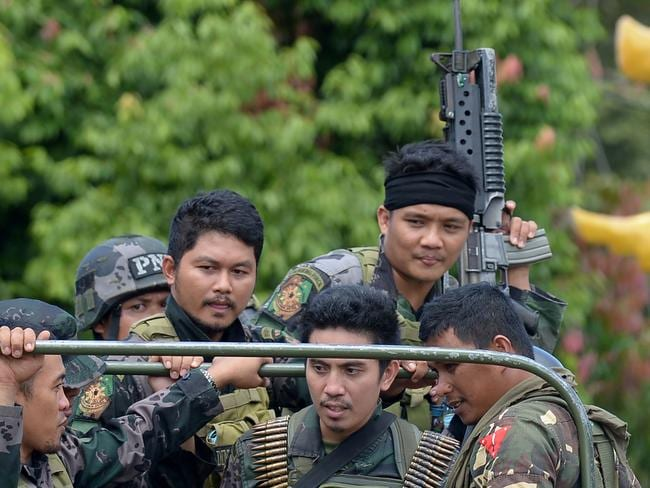 Members of the Philippine police special action force ride in an army truck on their way to the frontline in Marawi on the southern island of Mindanao last month. Picture: Ted Aljbe/AFP