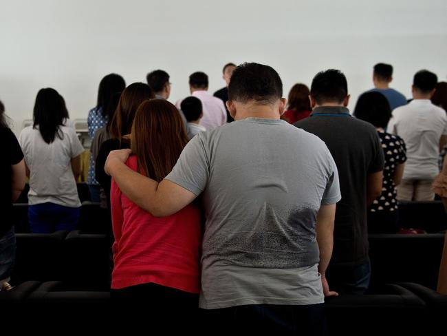 Relatives pray together inside a holding room at Juanda International Airport in Surabaya