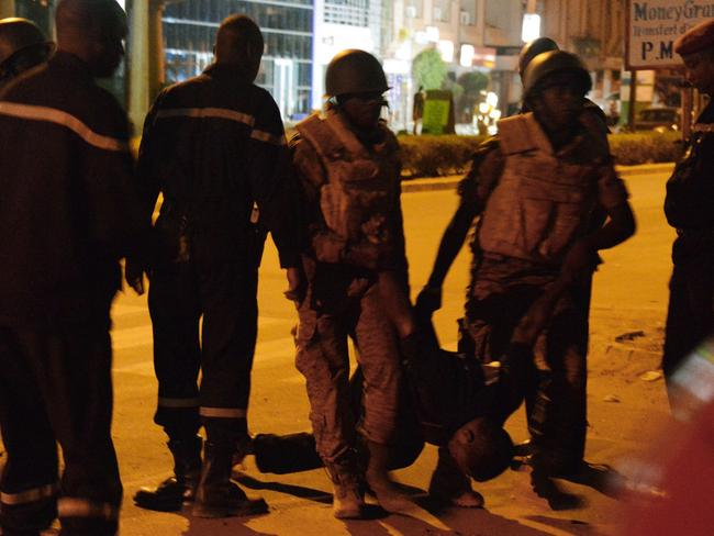 Violent attack ... Burkina Faso's soldiers carry the body of a man in the surroundings of the Splendid hotel. Picture: AFP