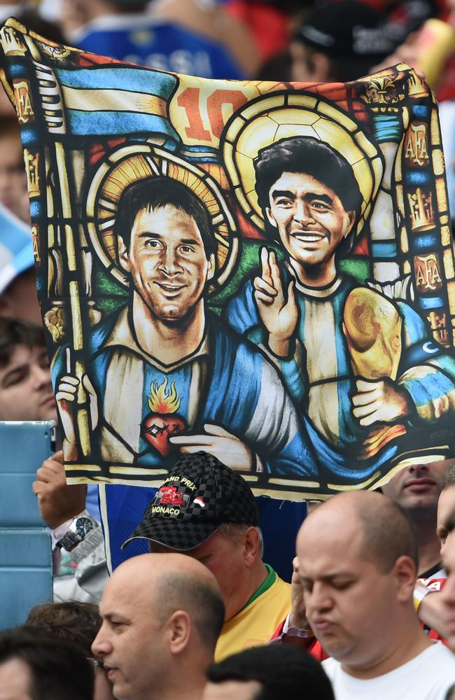 An Argentina fan holds an image of Argentina's forward Lionel Messi and former footballer Diego Maradona as Saints, before for the Group F football match between Nigeria and Argentina.