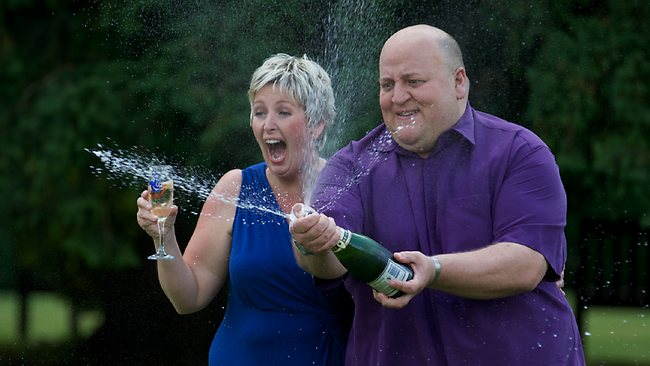 British Euro Millions winners Adrian (R) and Gillian Bayford spray champane during a photo call after winning £148,665,000 ($235 million) on the EuroMillions, in Hatfield Heath on August 14, 2012. A British couple who scooped a record 190 million euros in the EuroMillions lottery said Tuesday that they would carry on running their music shop and try to give their children a normal upbringing. AFP PHOTO / ANDREW COWIE