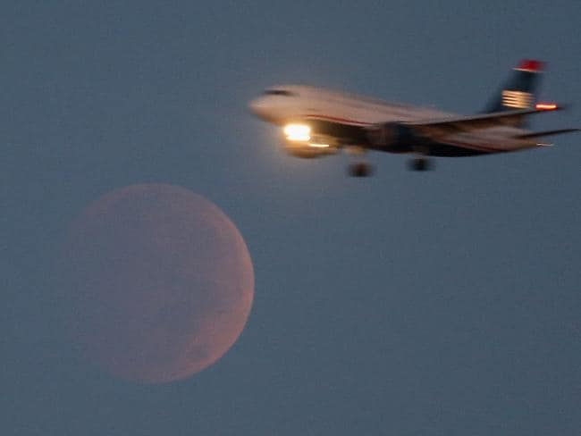 Full moon ... A commercial Airliner on approach to Reagan National Airport flies past the moon during a lunar eclipse as seen from Washington, DC. Picture:/Getty