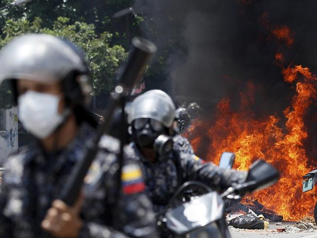 Venezuelan Bolivarian National police move away from the flames after an explosion at Altamira square. Picture: AP