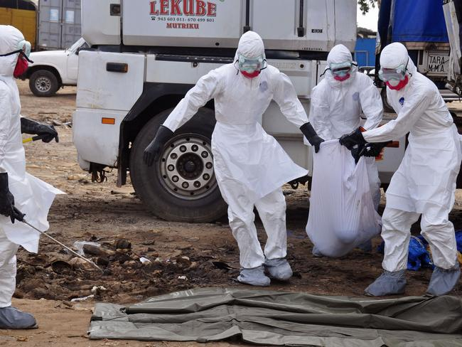 Bodies in the street ... health workers carry the body of a man suspected of dying from the Ebola virus and left in the road, in the capital city of Monrovia, Liberia. Picture: AP
