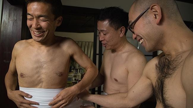 Nervous smiles while a strapping young man gets dressed for the Hadaka Matsuri. (Photo by