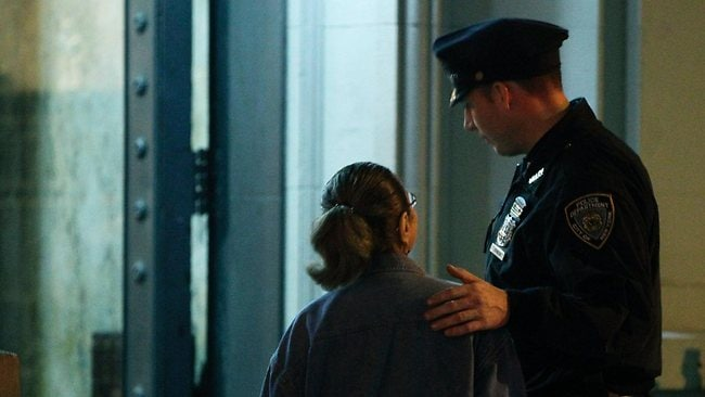 A New York City police officer comforts a woman in front of the luxury Manhattan apartment building where police say a nanny stabbed two small children to death. Picture: Kathy Willens