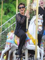Letting loose at a street fair in Paris Kris Jenner rides on the merry go round by the Eiffel tower after dinner at L'Avenue. Picture: Splash