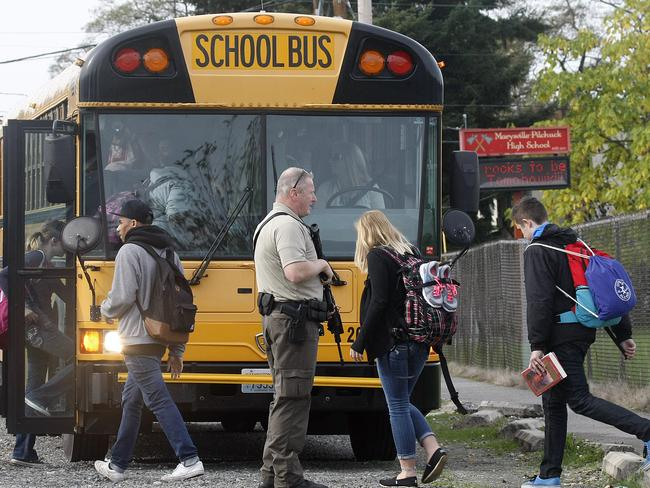 Students are evacuated from and loaded into school buses following the tragedy.