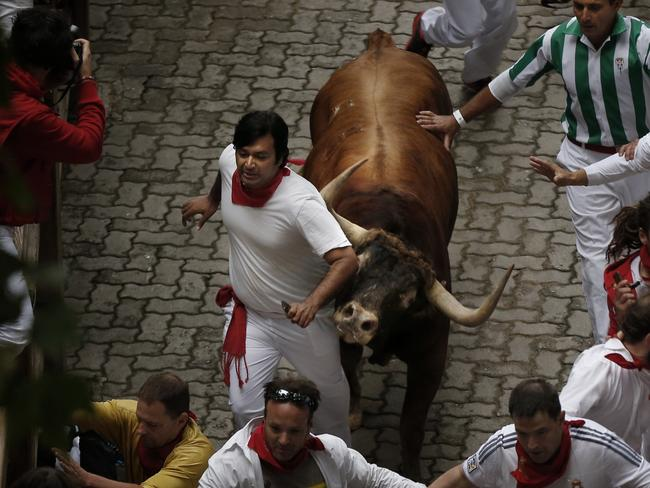 Close call ... A Victoriano del Rio ranch fighting bull stampedes during the running of the bulls of the San Fermin festival, in Pamplona. Picture: AP