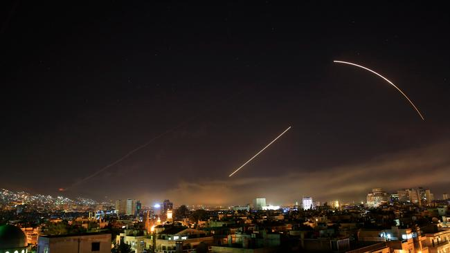 Missiles streak across the Damascus skyline as the US launches an attack on Syria targeting different parts of the capital on Saturday. Picture: AP /Hassan Ammar.