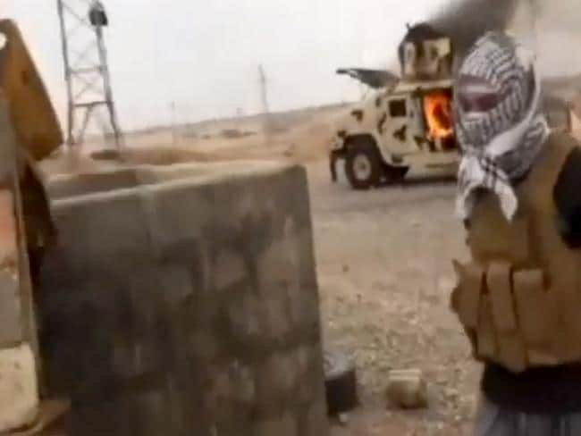 Baghdad is next ... This image made from video posted by IraqiRevolution, a group supporting the al-Qaeda breakaway Islamic State of Iraq and the Levant (ISIL) shows a militant standing in front of a burning Iraqi Army Humvee in Tikrit, Iraq.