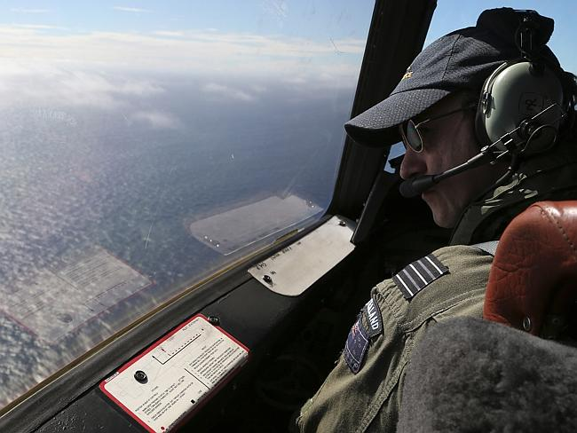 Search ... RNZAF Orion captain Wing Commander Rob Shearer looks out of the window of his aircraft while searching for missing Malaysia Airlines Flight MH370 near Perth. Picture: Gettty