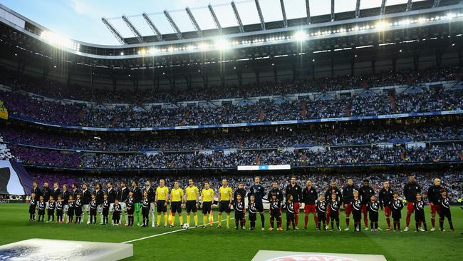 The Real Madrid and Bayern Munich teams line up with the officials.