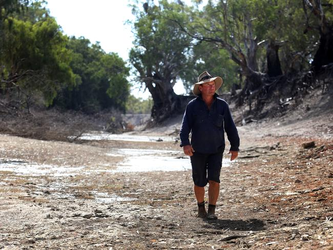 Farmer Wayne Smith walks along a dry section of the Darling River on his property, Karoola station, south of Menindee. Picture: David Geraghty