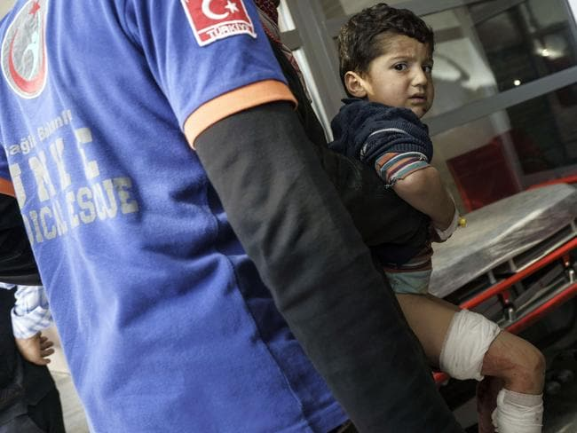 Injured ... Turkish medics carry a wounded Syrian boy to a hospital in Kilis after an air strike in the northern Syrian province of Idlib destroyed a makeshift clinic. Picture: AP Photo/Halit Onur Sandal