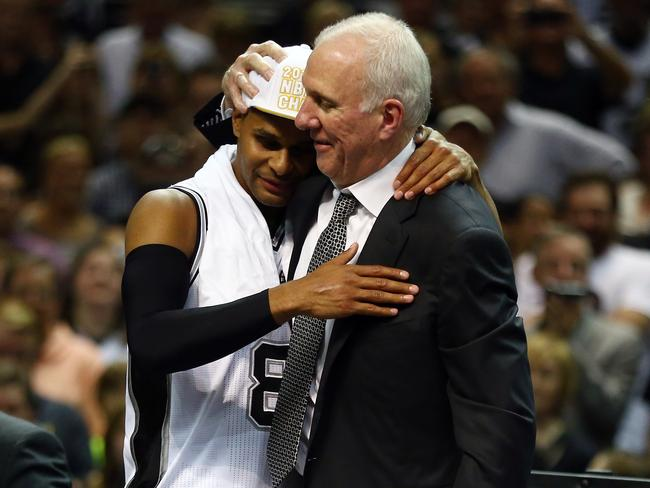 Patty Mills and Spurs coach Gregg Popovich share a hug after winning Game Five of the NBA Finals.