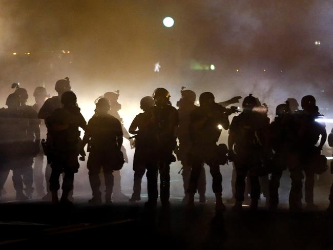 Call for calm ... Police walk through a cloud of smoke as they clash with protesters in Ferguson, Missouri.