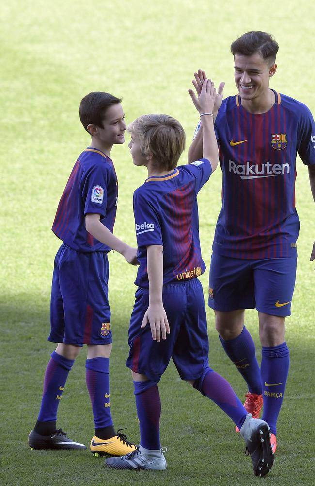 Barcelona's new Brazilian midfielder Philippe Coutinho cheers two boys