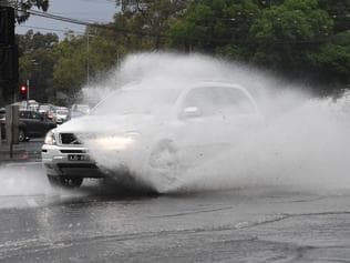 Cars are seen passing through the water covered intersection of Racecourse road and Flemington road in Melbourne on Saturday, November 18, 2017. A large storm has hit Melbourne bringing heavy rainfall and lightning. (AAP Image/James Ross) NO ARCHIVING
