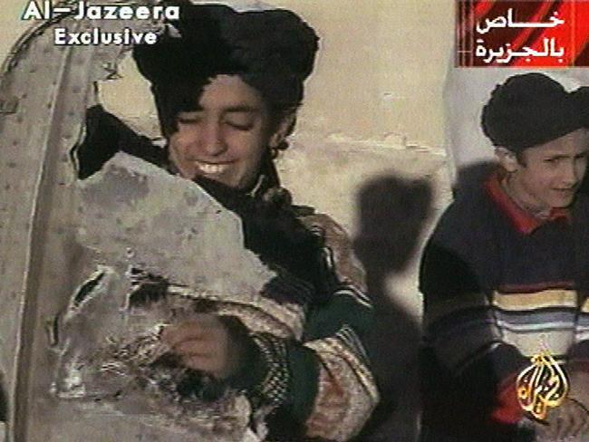 A young boy identified as Hamza bin Laden holds what the Taliban says is a piece of US helicopter wreckage in Ghazni, Afghanistan in 2001. Picture: AP Photo/Al-Jazeera via APTN