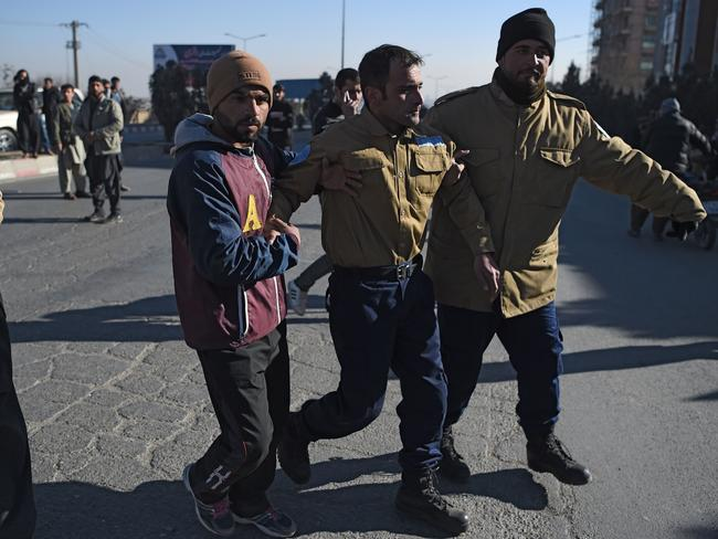 Afghan security from a private company assist an injured colleague near the Intercontinental Hotel following an attack by gunmen in Kabul. Picture: AFP